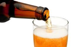 从在白色背景隔绝的瓶的倾吐的啤酒 免版税库存照片