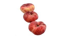 在白色背景隔绝的甜甜平的桃子 库存图片