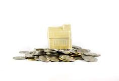 在白色背景隔绝的硬币顶部的议院 免版税库存图片