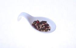 在白色背景隔绝的碗的混杂的黑,白色和红辣椒玉米 库存照片