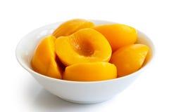 在白色背景隔绝的碗的罐装桃子一半 在每 免版税图库摄影