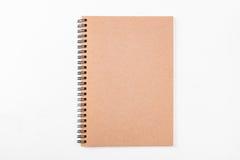 在白色背景隔绝的空白的棕色螺旋纸笔记本 库存图片