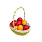 在白色背景隔绝的篮子的五颜六色的手工制造复活节彩蛋 免版税图库摄影