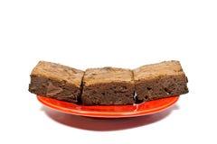 在红色盘的果仁巧克力蛋糕 免版税库存图片