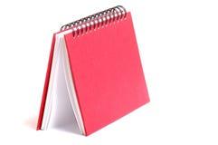 在白色背景隔绝的红色笔记本 免版税库存图片