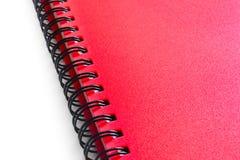 在白色背景隔绝的红色螺纹笔记本 库存照片