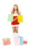 在白色背景隔绝的美丽的圣诞节女孩拿着五颜六色的包裹 免版税库存图片