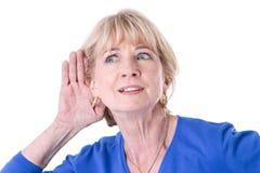 在白色背景隔绝的老妇人听力 免版税库存图片