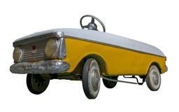 在白色背景隔绝的葡萄酒老玩具黄色白的脚蹬汽车 库存图片