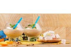 在白色背景隔绝的香蕉奶昔 异乎寻常的点心 土耳其快乐糖和圆滑的人在桌上 复制空间 库存照片