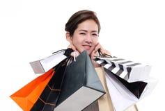 在白色背景隔绝的购物妇女亚洲愉快的微笑的举行的购物袋 库存图片