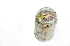 在白色背景隔绝的玻璃瓶子的硬币 库存照片