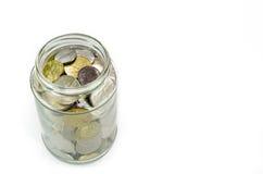 在白色背景隔绝的玻璃瓶子的硬币 库存图片