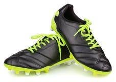 在白色背景隔绝的黑皮革橄榄球鞋子或足球起动 库存图片