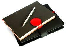在白色背景隔绝的黑笔记本,保护concep 免版税库存图片