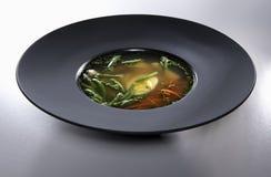 在白色背景隔绝的黑色的盘子的鸡肉汤 免版税库存照片