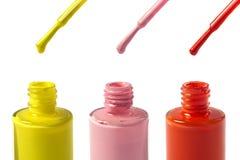 在白色背景隔绝的黄色,桃红色和红色指甲油瓶 免版税库存图片