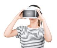 在白色背景隔绝的VR耳机的一个俏丽的女孩 创新技术 虚拟现实玻璃的一个女性游戏玩家 免版税库存图片