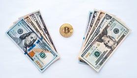 在白色背景,我们为一金属硬币bitcoin在纸币交换美元美元从隐藏货币 免版税库存照片