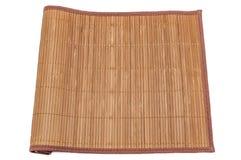 在白色背景,特写镜头的竹席子,卷起在一边 查出 免版税图库摄影