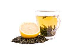 在白色背景绿茶隔绝的一个杯子 在裁减柠檬旁边的一个甜茶杯和自然绿色茶叶堆  免版税库存照片