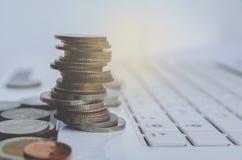 在白色膝上型计算机,计算机的堆硬币 财政和挽救 库存照片
