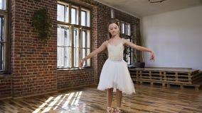 在白色芭蕾舞短裙火车温文地打扮的年轻亭亭玉立的芭蕾舞女演员在pointe芭蕾舞鞋在舞厅 优美的芭蕾舞女演员 股票录像