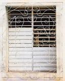 在白色花梢金属后部分地打开在窗口的白色快门 图库摄影