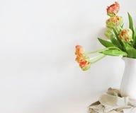 在白色花瓶的郁金香花束在木土气椅子 免版税库存图片