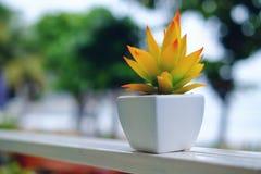 在白色花盆的人造花在阳台装饰 免版税图库摄影