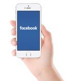 在白色苹果计算机iPhone 5s显示的Facebook商标在女性手上 库存照片