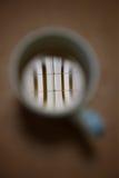 在白色茶的荧光灯管反射在桌上的 免版税库存照片