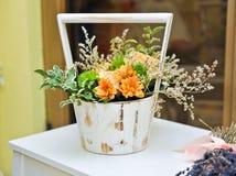 在白色葡萄酒罐的花的布置 与黄色花的婚礼装饰 免版税库存图片