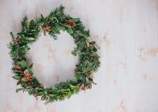 在白色葡萄酒背景的圣诞节花圈 免版税图库摄影