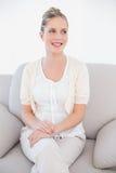在白色衣裳的微笑的新白肤金发的模型坐沙发 库存照片