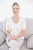 在白色衣裳的逗人喜爱的新白肤金发的模型坐沙发 库存图片