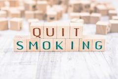 在白色表上的木块形成的词被放弃的抽烟,提示概念 免版税库存照片