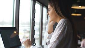 在白色衬衣打扮的年轻女实业家在咖啡馆在细胞坐在膝上型计算机前面的木桌上并且谈话 股票视频