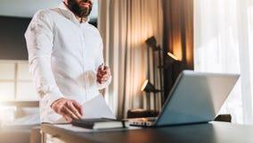 在白色衬衣的年轻有胡子的商人是在膝上型计算机,藏品文件前面的常设近的书桌 自由职业者工作 免版税库存图片