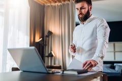 在白色衬衣的年轻有胡子的微笑的商人是在膝上型计算机,他的手文件的藏品前面的常设近的书桌 库存照片