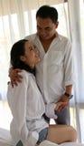 在白色衬衣的愉快的亚洲夫妇互相举行 免版税库存照片