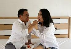 在白色衬衣的愉快的亚洲夫妇互相哺养在床上的果子 库存照片