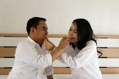 在白色衬衣的愉快的亚洲夫妇互相哺养在床上的果子 免版税库存图片