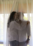 在白色衬衣的愉快的亚洲夫妇在帷幕后互相举行 免版税图库摄影