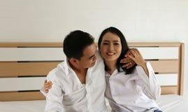 在白色衬衣的愉快的亚洲夫妇在床上互相举行 免版税图库摄影