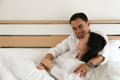 在白色衬衣的愉快的亚洲夫妇在床上微笑并且互相举行 免版税库存图片