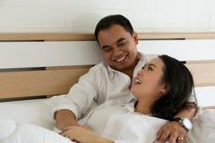 在白色衬衣的愉快的亚洲夫妇在床上微笑并且互相举行 免版税图库摄影