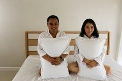 在白色衬衣的愉快的亚洲夫妇在床上的枕头 图库摄影