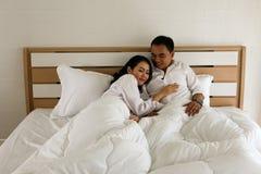 在白色衬衣的愉快的亚洲夫妇在床上睡觉 免版税库存照片