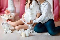 在白色衬衣的愉快的怀孕的夫妇坐地板,握大腹部预期一个婴儿,概念 免版税库存照片